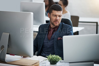 Buy stock photo Shot of a mature businessman using a computer and laptop at his desk in a modern office