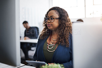 Buy stock photo Shot of a young businesswoman using a computer and digital tablet at her desk in a modern office
