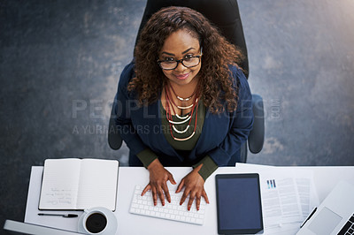 Buy stock photo High angle portrait of a happy young businesswoman at her desk in a modern office