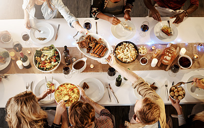 Buy stock photo High angle shot of friends getting together for a dinner party