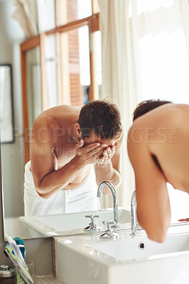 Buy stock photo Cropped shot of a shirtless young man washing his face by the bathroom sink