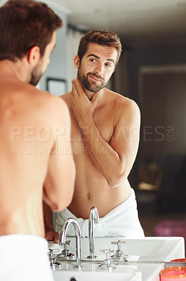 Buy stock photo Cropped shot of a shirtless young man checking out his skin in the bathroom mirror