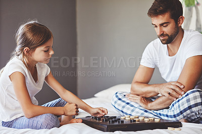 Buy stock photo Cropped shot of a young father playing a board game with his adorable little daughter at home