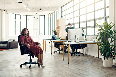 Buy stock photo Portrait of a young businesswoman sitting in a modern office with her colleagues working in the background