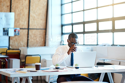 Buy stock photo Shot of a focused young businessman typing on his laptop and drinking coffee while being seated at his desk in the office at work during the day
