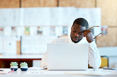 Buy stock photo Shot of a focused young businessman typing on his laptop and contemplating while being seated at his desk in the office at work during the day
