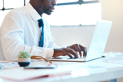 Buy stock photo Shot of an unrecognizable businessman typing on his laptop while being seated at a desk in the office during the day