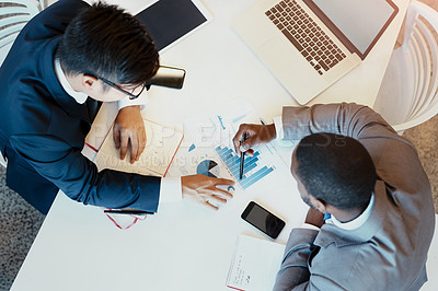 Buy stock photo High angle shot of two young focused businessman making notes while looking at graphs inside the office at work