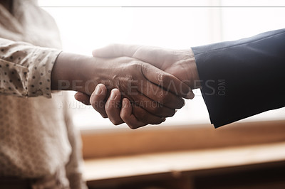 Buy stock photo Closeup shot of two unrecognisable businesspeople shaking hands in an office