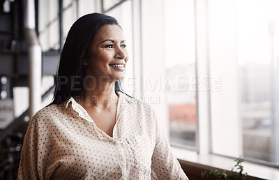 Buy stock photo Shot of a mature businesswoman looking out a window in an office