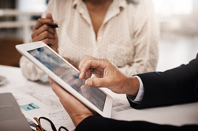 Buy stock photo Closeup shot of two unrecognisable businesspeople analysing graphs on a digital tablet in an office