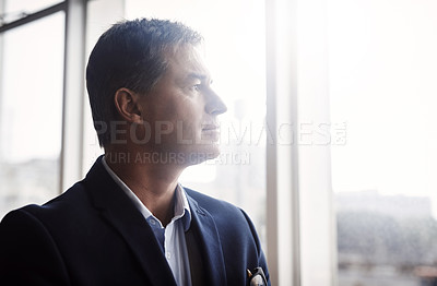 Buy stock photo Shot of a mature businessman looking out a window in an office