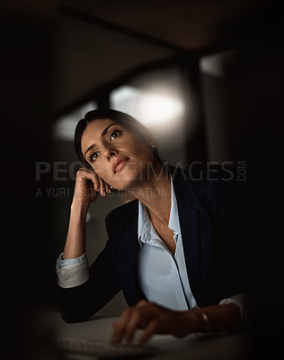 Buy stock photo Shot of a young businesswoman looking thoughtful during a late night in a modern office