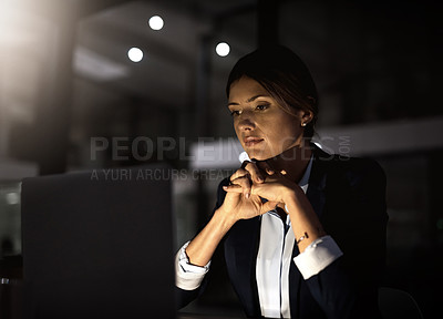 Buy stock photo Shot of a young businesswoman using a laptop during a late at night in a modern office