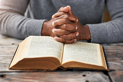 Buy stock photo High angle shot of an unrecognizable man reading his bible while sitting outside