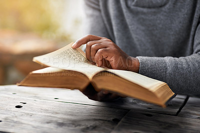 Buy stock photo Cropped shot of an unrecognizable man reading his bible while sitting outside