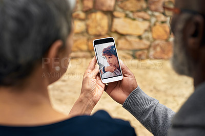 Buy stock photo Rearview shot of an affectionate senior couple taking selfies while sitting in the park
