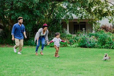 Buy stock photo Shot of a little boy chasing a squirrel while at the park with his parents