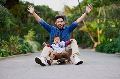 Buy stock photo Shot of a young man and his son on a skateboard