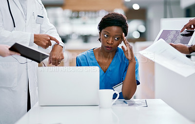 Buy stock photo Shot of a young doctor looking stressed out in a demanding work environment