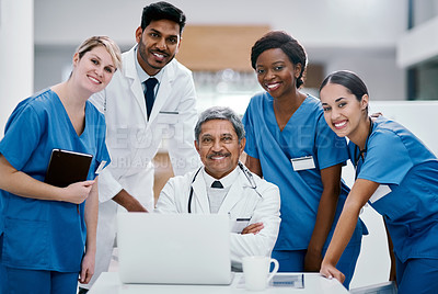 Buy stock photo Portrait of a group of medical practitioners working together on a laptop in a hospital