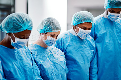 Buy stock photo Shot of a group of surgeons performing a surgery in an operating theatre