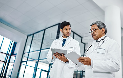 Buy stock photo Shot of two medical practitioners using a digital tablet together in a hospital