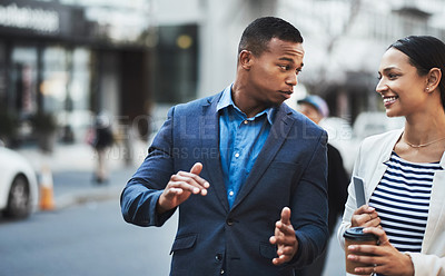 Buy stock photo Shot of two businesspeople having a discussion while walking in the city