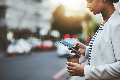 Buy stock photo Shot of a young businesswoman using a cellphone in the city