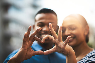 Buy stock photo Cropped shot of a young couple making a heart gesture with their hands outdoors