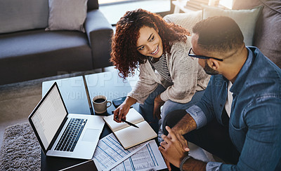 Buy stock photo Cropped shot of a young couple doing their finances at home