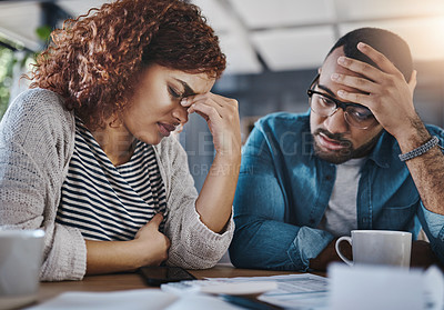 Buy stock photo Shot of a young couple looking stressed out while working on their budget at home