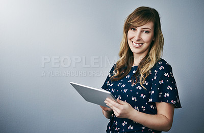 Buy stock photo Studio portrait of an attractive young woman using her digital tablet against a grey background