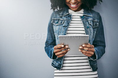 Buy stock photo Studio shot of an unrecognizable young woman using her digital tablet against a grey background