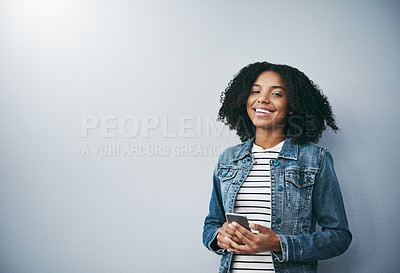 Buy stock photo Studio portrait of an attractive young woman using her cellphone against a grey background