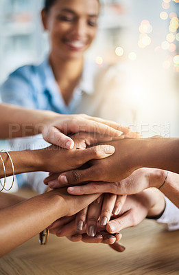 Buy stock photo Cropped shot of a group of young businesspeople sitting in the boardroom with their hands in a huddle