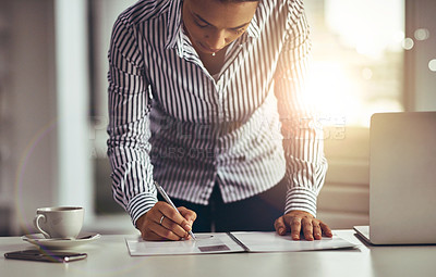 Buy stock photo Shot of a young businesswoman writing notes on a document in an office