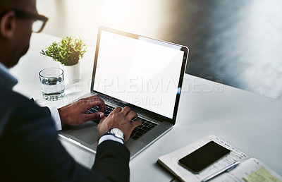 Buy stock photo High angle shot of an unrecognizable young businessman working on his laptop in a modern office