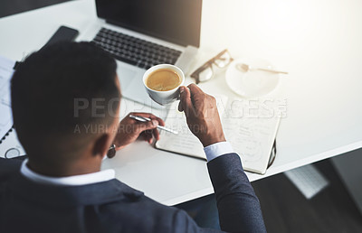 Buy stock photo High angle shot of an unrecognizable young businessman drinking coffee while working in his modern office