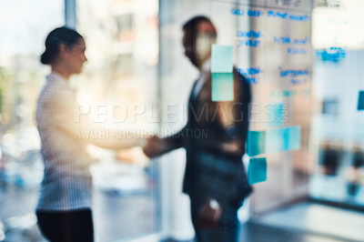 Buy stock photo Defocused shot of two businesspeople shaking hands in an office