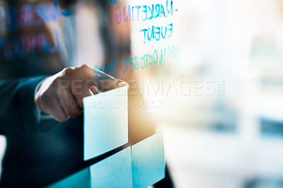Buy stock photo Closeup shot of an unrecognizable businessman pointing to notes on a glass wall in an office