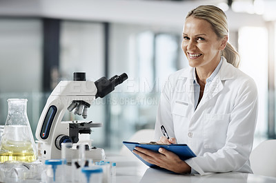 Buy stock photo Cropped portrait of an attractive mature female scientist taking down notes while doing research in her lab