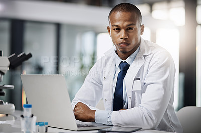 Buy stock photo Cropped portrait of a handsome young male scientist working on a laptop while doing research in his lab