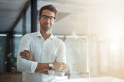 Buy stock photo Cropped portrait of a handsome young businessman standing with his arms folded in the office