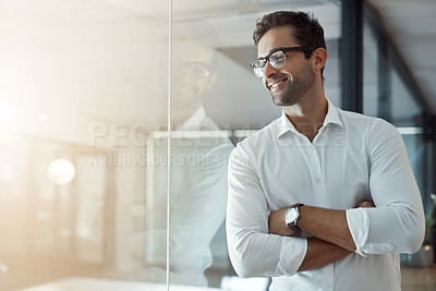 Buy stock photo Cropped shot of a handsome young businessman looking thoughtful while standing with his arms folded in the office