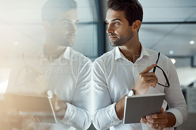 Buy stock photo Cropped shot of a handsome young businessman looking thoughtful working on his digital tablet while standing in the office