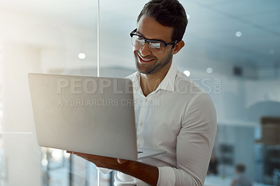 Buy stock photo Cropped shot of a handsome young businessman working on his laptop while standing in the office