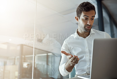Buy stock photo Cropped shot of a handsome young businessman looking unsure while working on his laptop in the office
