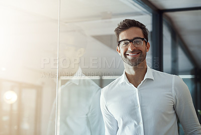 Buy stock photo Cropped portrait of a handsome young businessman leaning against a glass wall in his modern office