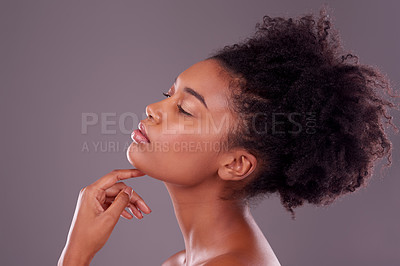 Buy stock photo Studio shot of a beautiful young woman posing against a purple background